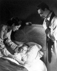 Parents with sick child  1940s.