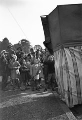 Children watching a Punch and Judy show  c