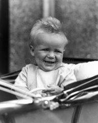 Baby sitting in a pram  c 1930s.