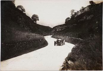 Motor car on a winding road  c 1912.