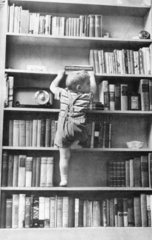 Child climbing a bookshelf  c 1977.