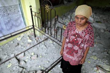 Kampung Bedang  Indonesien  eine Frau neben dem Bettgestell in ihrem zerstoerten Haus