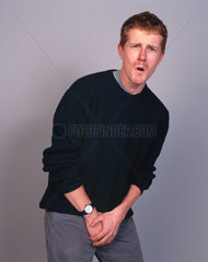 Man clutching his testicles and wincing with pain  December 2000.