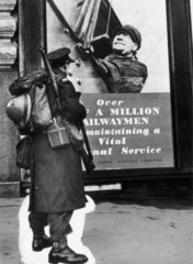 Soldier standing in front of a poster  Second World War  1939-1945.