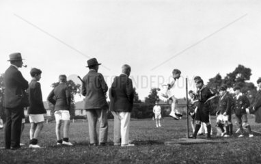 Schoolboy doing the high jump on sports day  c 1920s.