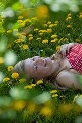 Freiburg  Deutschland  eine junge Frau liegt im Gras zwischen Loewenzahn