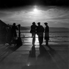 Figures silhouetted by the moon on a promenade  c 1930s.