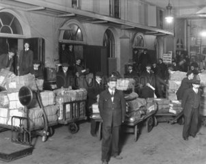 Newspapers being loaded onto a train  Paddington Station  London  c 1910.