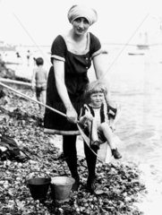 Young woman holding child in fishing net at