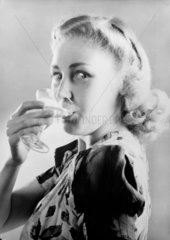 Woman drinking a glass of champagne  1949