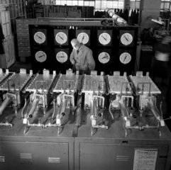 Worker examines hydrogen furnaces and control panels  GEC  1956.