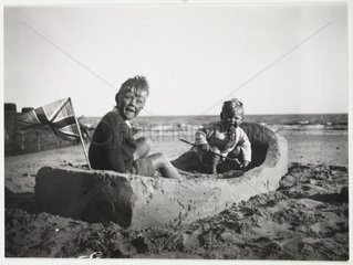 Two children in a sand boat  c 1930.