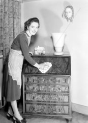 Woman polishing a chest of drawers  1952.
