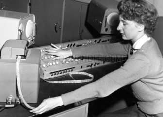 Female computer operator feeding instructions to 'The Brain'  May 1955.