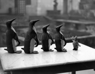 A toy policeman with some toy penguins