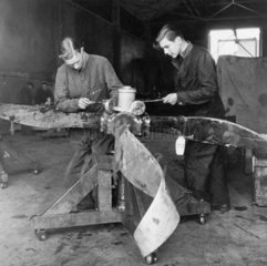 Two men repairing a Royal Air Force propell