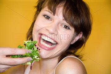 Freiburg  Deutschland  eine junge Frau isst Salat mit den Haenden