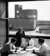 Four research chemists by window with main CIBA plant in distance.
