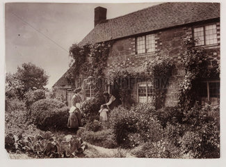 Mothers outside a cottage  c 1890.