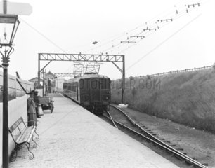 Electric locomotive and train at a station  1913.
