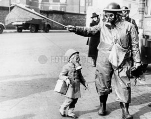 Child and warden wearing gas masks  London  27 March 1941.