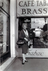 Woman standing outside a brasserie  France  1950s.