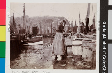 Scottish fishergirls gutting herring on Scarborough quayside  c 1900s.
