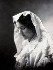 Woman wearing a white headdress gazing downward  c 1890s.