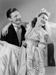 Groom carrying his bride  c 1949.