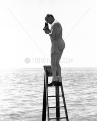 Zoltan Glass taking a photograph standing on a ladder in the sea  c 1964.