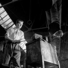Low angle shot of Lemington glassworker turning glass bulb  1960.