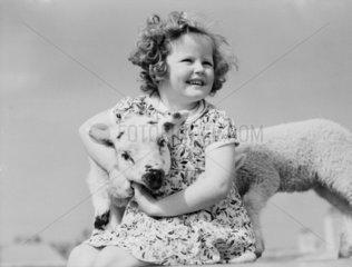 Girl cuddling a lamb.