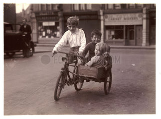Children riding a bicycle and sidecar  c 1930.
