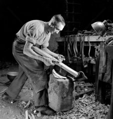 A cooper at Cannon Brewery cooperage planing a section for a barrel  1948.