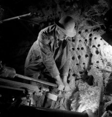 A miner guides a drill in to a rock underground  Holman Brothers  1948.