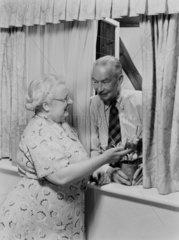 Elderly couple talking at a window  c 1950