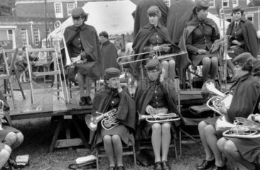 Band of women musicians in uniform  preparing to play at a festival  1969.