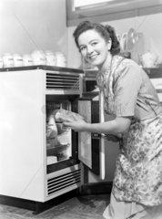 Woman opening a fridge  1950.