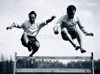Two men jumping a steeplechase hurdle  c 1920s.