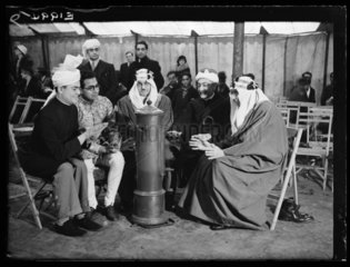 Muslim leaders warming themselves at a heater  Woking  6 January 1935.