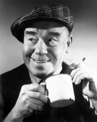 Man having a cup of tea and a cigarette  c 1940s.