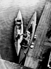 Two young men in kayaks alongside a jetty  c 1920s.