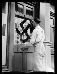 Removing swastika graffiti  1938.