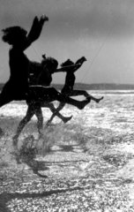 Silhouetted children jumping into the sea