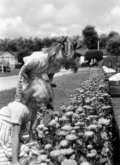Two young girls smelling flowers  c 1930s.