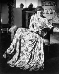 Woman wearing a full-length floral dress  1940s.