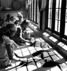 Women examining sifted tea at a tea factory