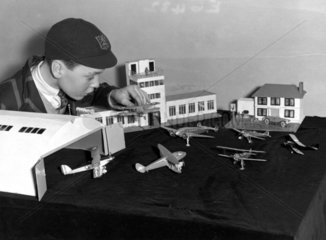 A boy plays with toy aeroplanes being sold