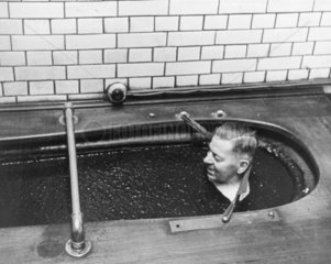 Man relaxing in a peat bath  15th December 1960.