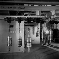 Fitter examines completed engine shafts as they hang from racks  Bradford  1959.